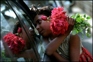 A girl selling flowers on the side of the street
