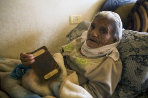 Absiya Jafari, aged more than 100 years old, holds a Palestinian passport issued during the British Mandate belonging to her husband and herself, in the West Bank village of al-Walaja, 23 November. The original village of al-Walaja was completely destroyed by Zionist forces in 1948. (Anne Paq / ActiveStills)